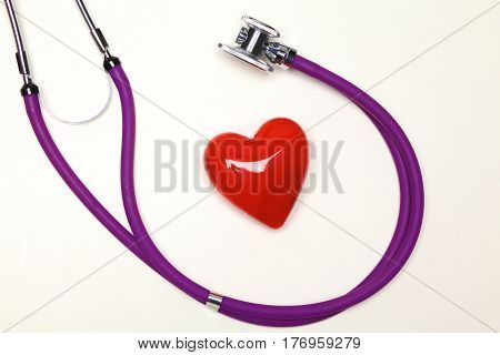 Medical stethoscope and red heart on a white table.