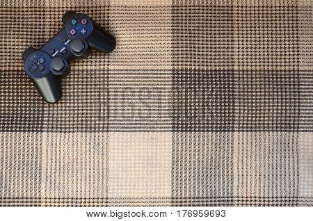 Video Game Controller Lies On A Checkered Plaid