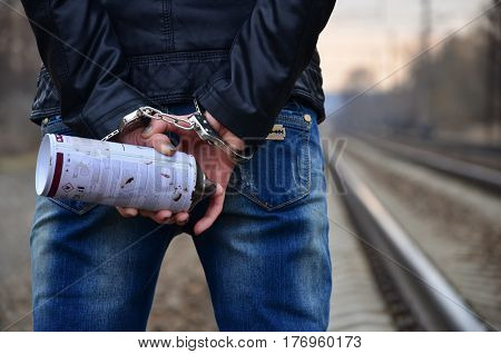Girl In Handcuffs With Spraycan On The Background Of A Railway Track