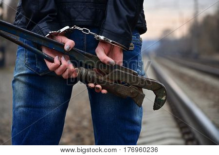 The Girl In Handcuffs With The Pipe Wrench On The Railway Track Background