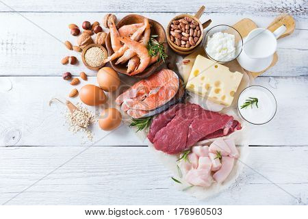 Assortment of healthy protein source and body building food. Meat beef salmon shrimp chicken eggs dairy products milk cheese yogurt beans quinoa nuts oat meal. Copy space background, top view