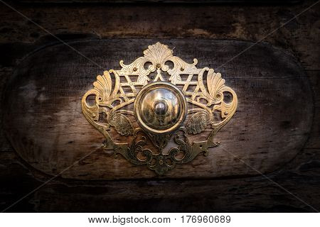 Golden metal decoration on the door of a Roman church used to protect the door and do not bump into the wall when it opens.