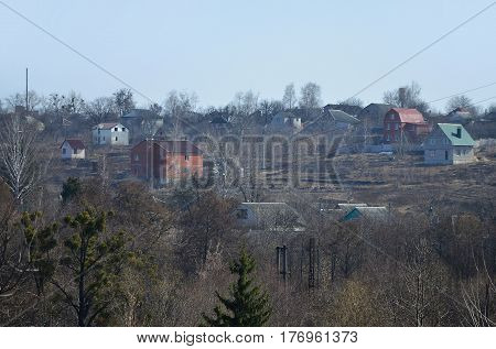 A country landscape with many rural cottages trees and green spaces. Many houses are located near each other in the spring village