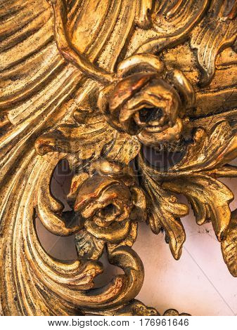 Detail of gilded wooden frame of an antique mirror.