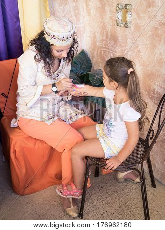 Verona Italy - September 8 2015: Girl paints a washable tattoo on the arm of a child.