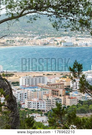 view through trees from high point hills into St Antoni de Portmany & surrounding area in Ibiza.  on nearby hillside.
