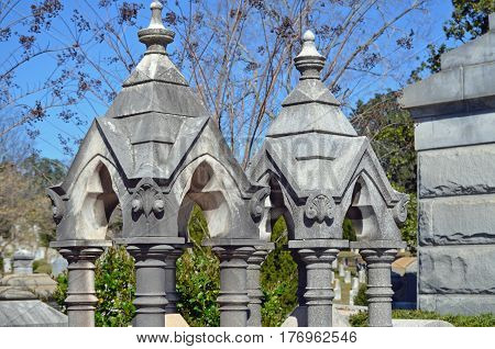 Ornate cemetery monuments made of pillars and roof-like tops