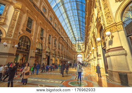 MILAN, ITALY- MARCH 7, 2017: tourists walking for shopping inside the Galleria Vittorio Emanuele II gallery in Piazza Duomo square. Famous fashion stores like Prada. Luxury and shopping concept.