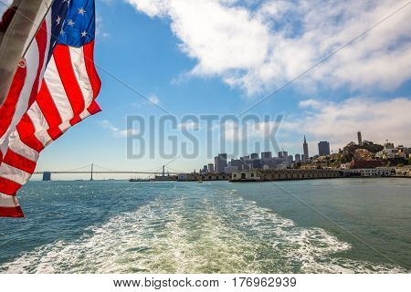 San Francisco Financial District cityscape and Oakland Bridge on sunny day, California, United States. Sea views from Alcatraz boat with American flag waving. Freedom and travel concept.