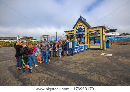 San Francisco, California, United States - August 14, 2016: row of tourists for Ferries and Bay Tours ticket to San Francisco Bay. Leisure, holidays and travel concept. Fisherman's Wharf waterfront.