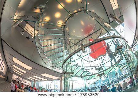 Hong Kong, China - December 4, 2016: fish-eye interior prospective view inside Apple store with glass stairway, IFC Mall, customers looking for best new technological products.