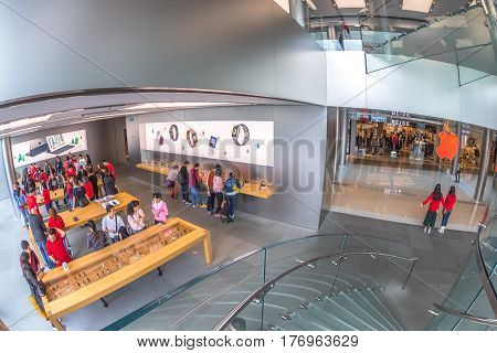 Hong Kong, China - December 4, 2016: fish-eye aerial view of Apple store of IFC Mall, with customers looking the new technological products and shop clerks in red.
