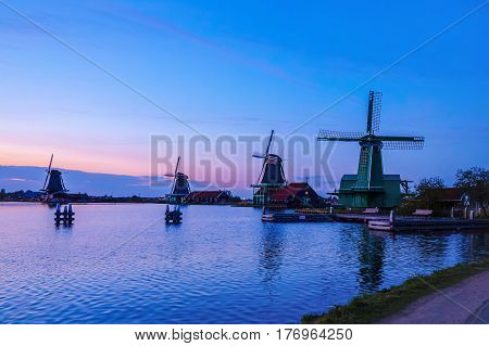 Dutch mill by evening. Sunset in landscape with mill the Netherlands. Dutch windmill at sunset at a lake. River Zaan with four windmills lined up at 'De Zaanse Schans' in Zaandam, Netherlands