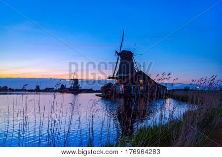 Evening River Zaan with Dutch windmills in Zaandam, Netherlands. Sunset landscape with windmills and field wild herbs and flowers. Sunset landscape with windmills and field wild herbs and flowers.