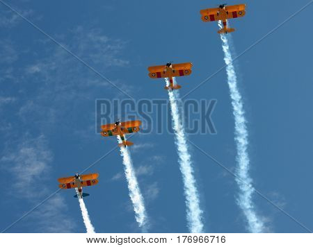 Four Biplanes Climbing in Unison with Smoke Trails
