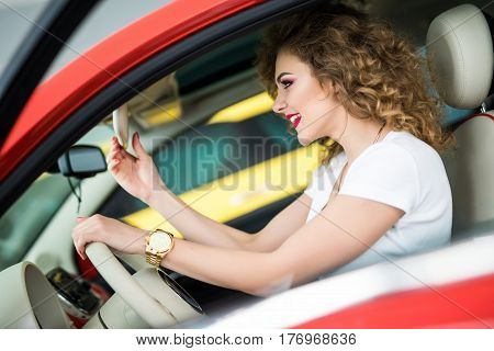 Side View Of Nice Stylish Girl Touching A Rear View Mirror And Smiling While Driving The Car