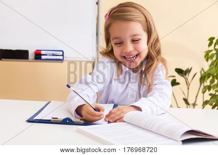 Beautiful little girl with wavy hair writes sitting at table