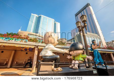 Hong Kong, China - December 5, 2016: Cowboy and Bruce Lee, statues of famous characters, Hong Kong Avenue of Comic Stars, Kowloon Park. Urban skyline of Tsim Sha Tsui District.