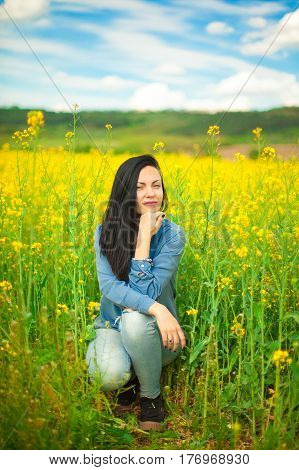 Portrait of young happy woman in rapeseed field. Springtime.