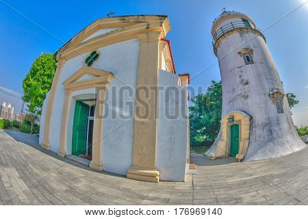 Fish-eye view of iconic Guia Lighthouse, Fortress and Chapel in Historic Centre of Macau, China. Sunny day, blue sky. Unesco Heritage Site.