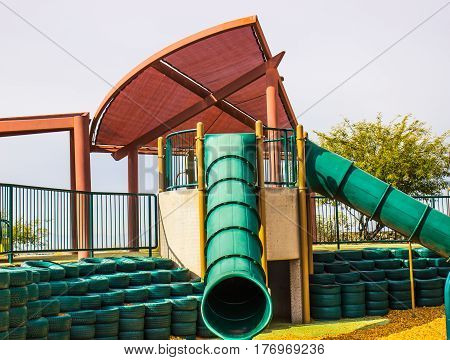Two Tube Slides & Rubber Tire Bumpers At Playground