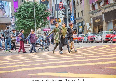 Hong Kong, China - December 6, 2016: typical asian familes and friends, crossing the Times Square intersection, largest shopping mall in Causeway Bay, the luxury shopping district.
