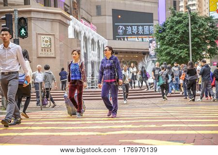 Hong Kong, China - December 6, 2016: asian women tourists with luggage side walking the Times Square intersection, largest shopping mall in Causeway Bay, the luxury shopping district.