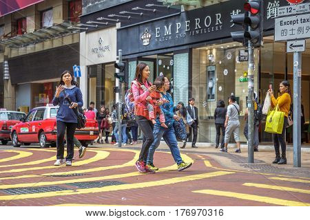 Hong Kong, China - December 6, 2016: asian woman with baby and grandmother, in the Times Square street, largest shopping mall in Causeway Bay, the luxury shopping district.