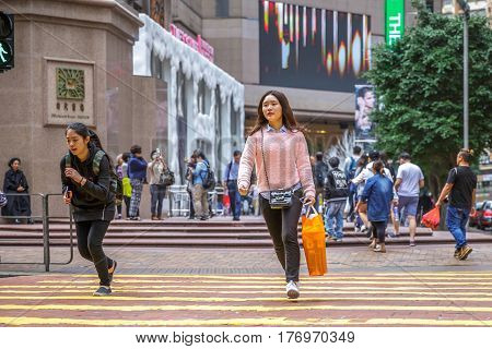 Hong Kong, China - December 6, 2016: Causeway Bay, the most attractive area for business people and shopping. Typical Asian elegant fashion woman with shopping bag crossing the street happy.