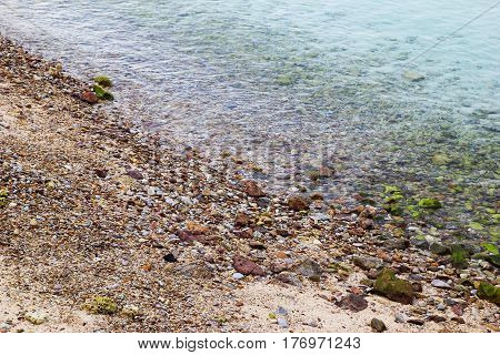 Travel to island Koh Larn Thailand. The seashore with stones and blue clear water.
