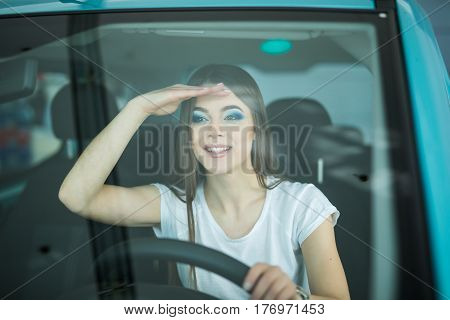 Smiling woman driving car looking streight front