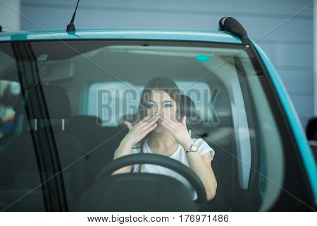 Beautiful Smiling woman driving car, shocked with hands on mouth