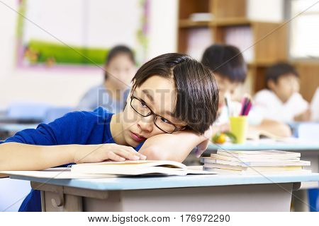 asian elementary school boy resting his head on desk and thinking.