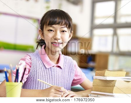 portrait of a happy elementary school girl looking at camera smiling.