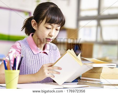 asian primary school pupil reading a book in classroom.