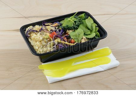 Take out chicken and rice salad with plastic knife and fork for portable lunch at work or on the go