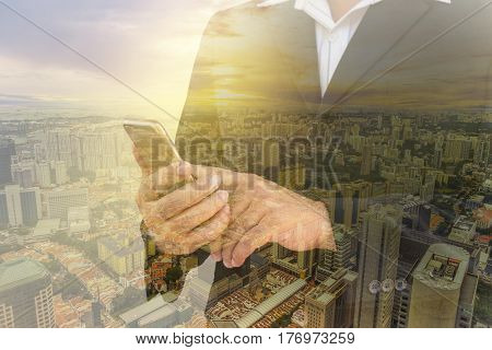 double exposure of businessman check his smartphone and cityscape and sun light filter - can use to display or montage on product
