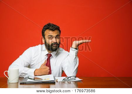 Bearded indian businessman sitting at table and presenting something with left hand, pointing towards blank wall with copyspace, asian business person presenting something