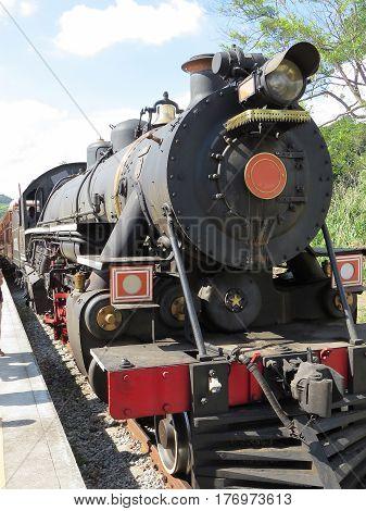 Locomotiva de trem a vapor, parada em pequena estação de linha ferrea, aguardando a próxima partida, no campo, Brasil