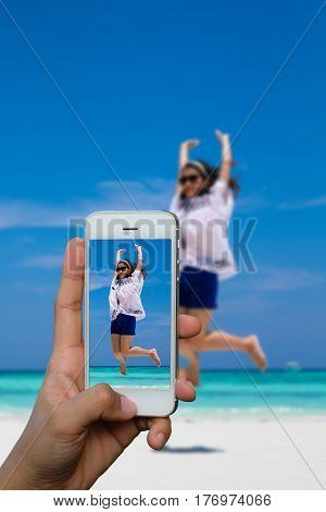Smartphone photographing Asia woman in jumping action Similan Island Koh Ta Chai Andaman Sea Thailand