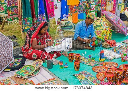 Kolkata West Bengal India - 28th November 2015 : Couple hand coloring pen stands made of clay and clothes handicrafts on display during the Handicraft Fair in Kolkata. Biggest handicrafts fair in Asia.