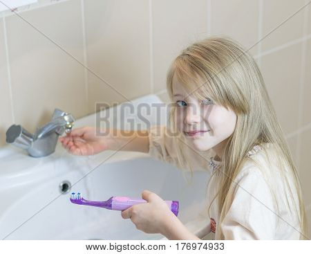 A Girl Washes An Electric Toothbrush In The Bathroom.