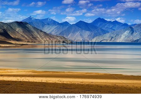 Mountains and Pangong tso (Lake). It is huge lake in Ladakh altitude 4350 m (14270 ft). It is 134 km (83 mi) long and extends from India to Tibet. Leh Ladakh Jammu and Kashmir India