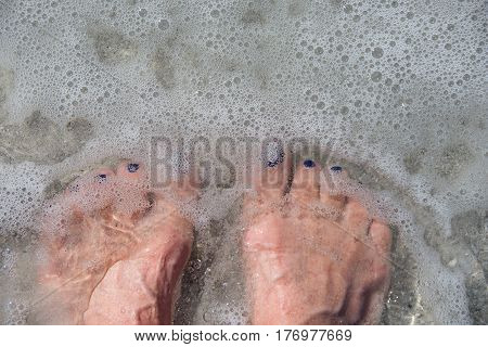 bare feet in frothy ocean water and beach sand