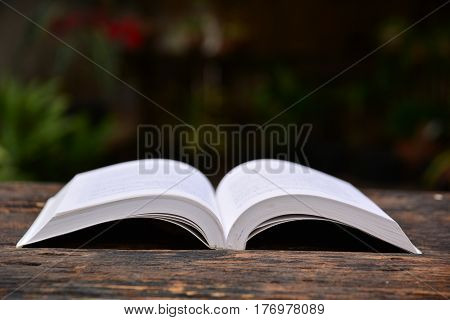 the book put on wooden table on dark background