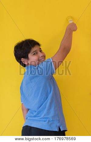 Portrait of a young boy painter with a brush in his hand in front of colored background