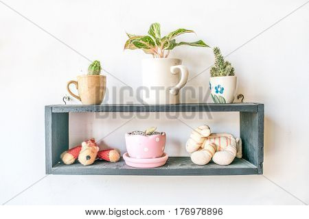 small doll and  small plant in pot decoration on wood frame isolated white background