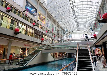 Singapore, Singapore - February 10, 2017: People walk at the Marina Bay Sands Shoppes, decorated for China New Year, on sunny day in Singapore.