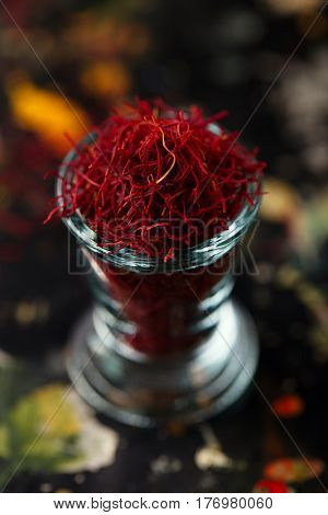 saffron space threads in vintage glass bowl on dark metal background