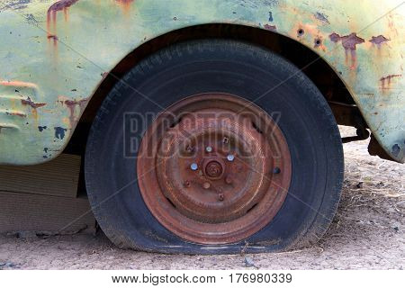 Close up.close up of a flat tire of a rusty old car on dirt road. Rusted wheel of old car.